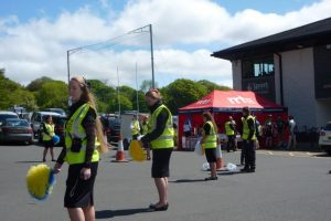 Volunteers cheer the cyclists as they reach the finish line before receiving refreshments from the RRT marquee.