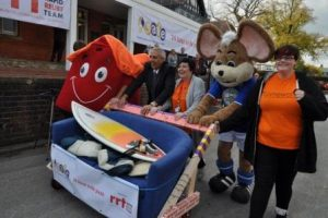 "SAFE housing mascot (left), Deputy Police Crime Commissioner, Hardyal Dhindsa (second from left), SAFE Service Manager & Consortia Lead, Sue Wood (Centre), with Chesterfield FC ""Chester the Mouse"" and Megan (a community member representing those the event was supporting) pushing the Sofa Surf."
