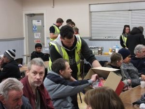 RRT member handing round food to hungry residents